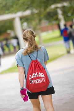 girl walking on campus with a Lamar backpack