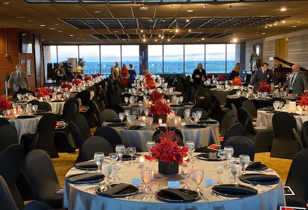 Room view of round tables, black chairs, black plates, red floral centerpieces