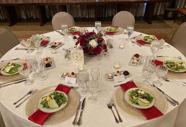 Round table, beige and red setting with salad on plates, square dessert plates with sweets, red floral centerpiece