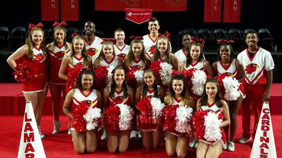LU 2018-2019 Cheer Team, men and women dressed in red and white LU cheer uniforms with poms and megaphones