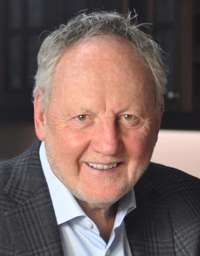 Michael Fullan smiling, wearing light blue shirt and gray striped jacket.