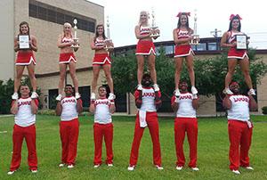 Cheerleaders stunting with trophies