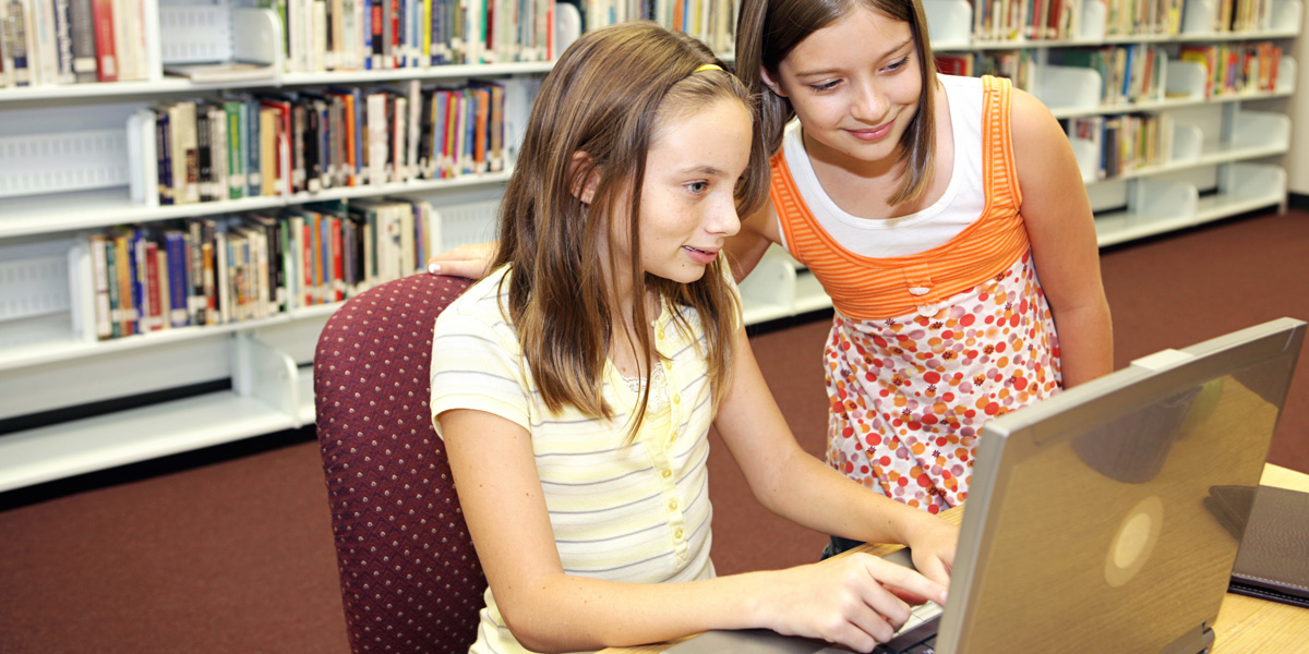 Two young girls computer coding