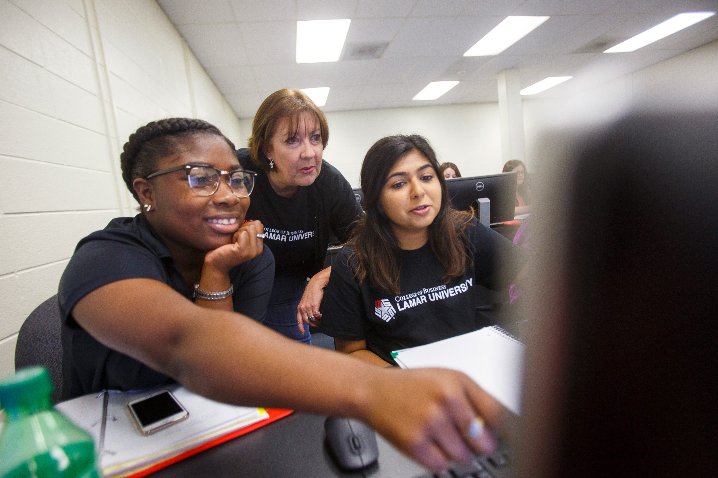 College of Business Students with professor working on a computer