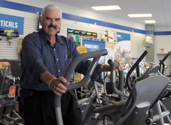 Rod Rice with fitness equipment in his store