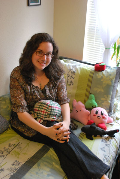 Kayleigh Romero sits in her dorm room with stuffed animals she made
