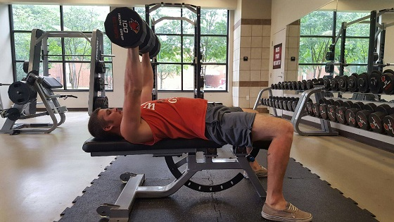 A Lamar student working out with dumbbells